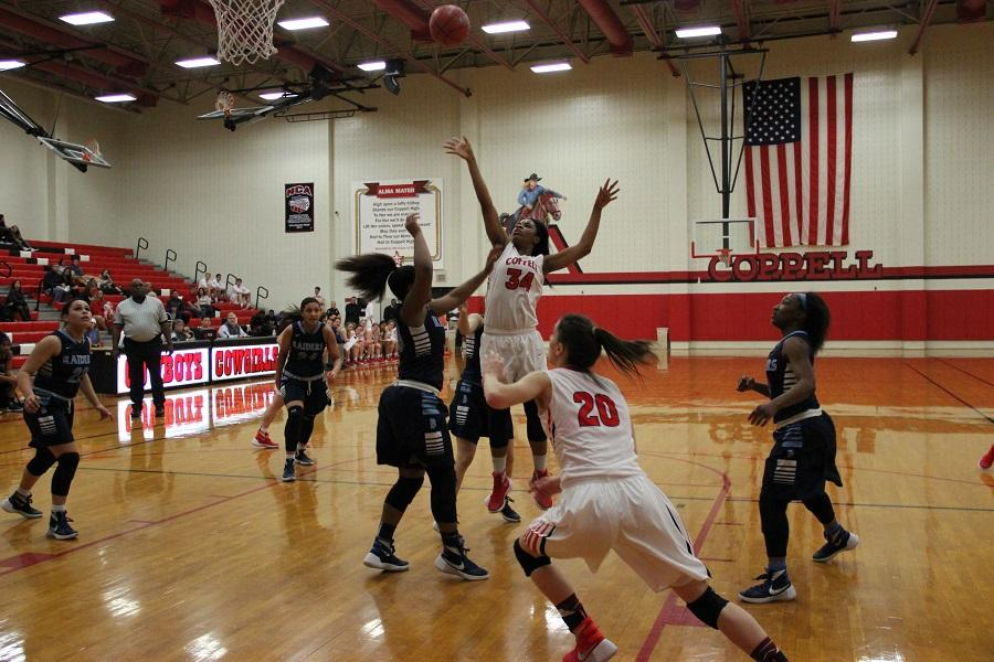 Coppell High School junior center Chidera Nwaiwu shoots the ball as a player from L. D. Bell attempts to defend the basket. The Cowgirls lost to the Lady Raiders 39-26.