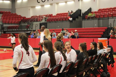 Coppell High School junior right side hitter Breanne Chausse turns around excitedly towards the crowd while sitting and waiting to be rotated into the game against W.T. White Tuesday night in the arena. Coppell won against W.T. White, greatly outscoring them. Photo by Hannah Tucker.