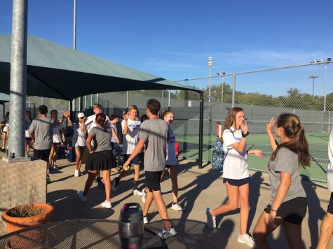 CHS tennis players exchange high-fives with Pierce High School players after winning 10-0 on Oct. 21. The CHS team will advance to regionals, hoping to continue their winning streak.