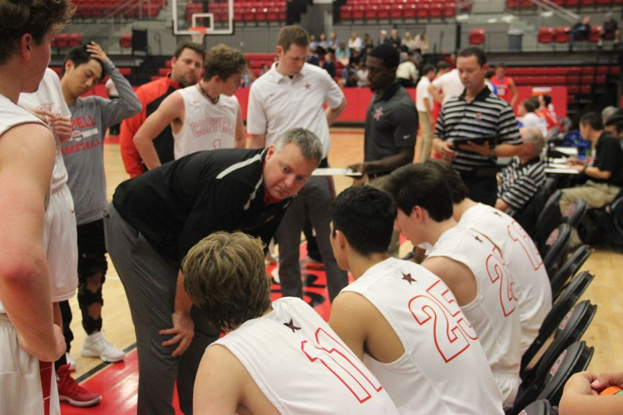 Coppell coach Kit Pehl talkins with his team during a timeout during the game on Tuesday. After a close game, the Mustangs claimed a victory over the Cowboys with a final score of 55-45.