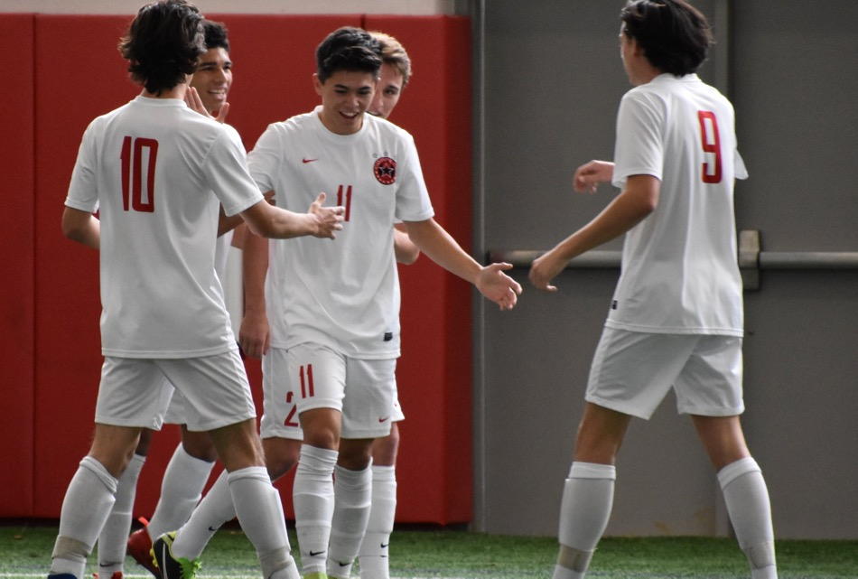 Coppell junior forward Wyatt Priest (10), senior forward Nick Taylor (11) and senior midfielder Alex Haas (9) celebrate Taylor's goal during the first half of Saturday's game in the Coppell indoor facility.  The Cowboys defeated El Paso Socorro 4-1 to win the North Texas Elite Showcase Tournament.