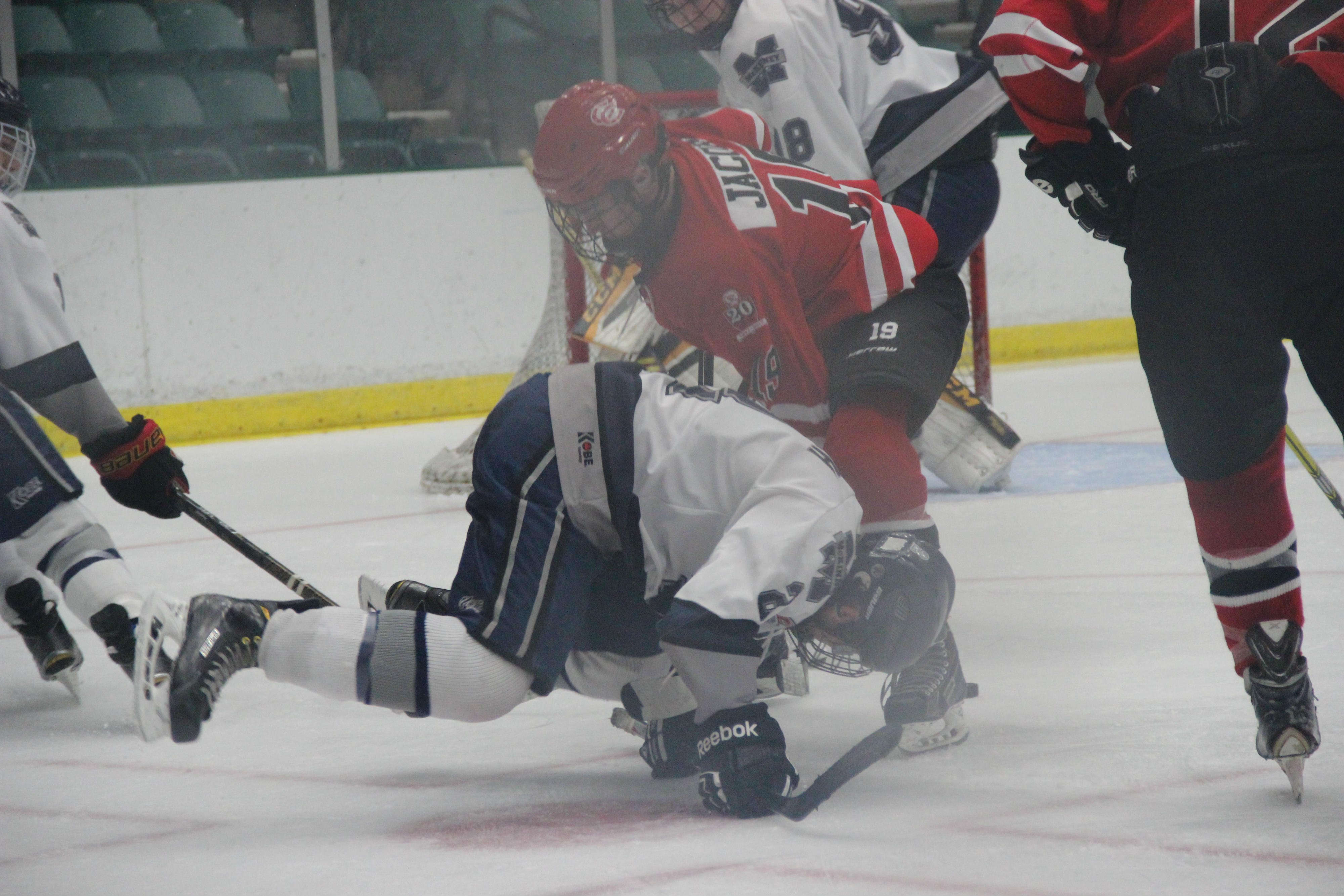 McKinney forward Patrick Conway falls to the ice in front of Coppell senior forward Collin Jacobs in Coppell's 4-2 loss to McKinney on Saturday at the Dr Pepper StarCenter in Frisco. With the loss, the Cowboys were eliminated from state title contention.