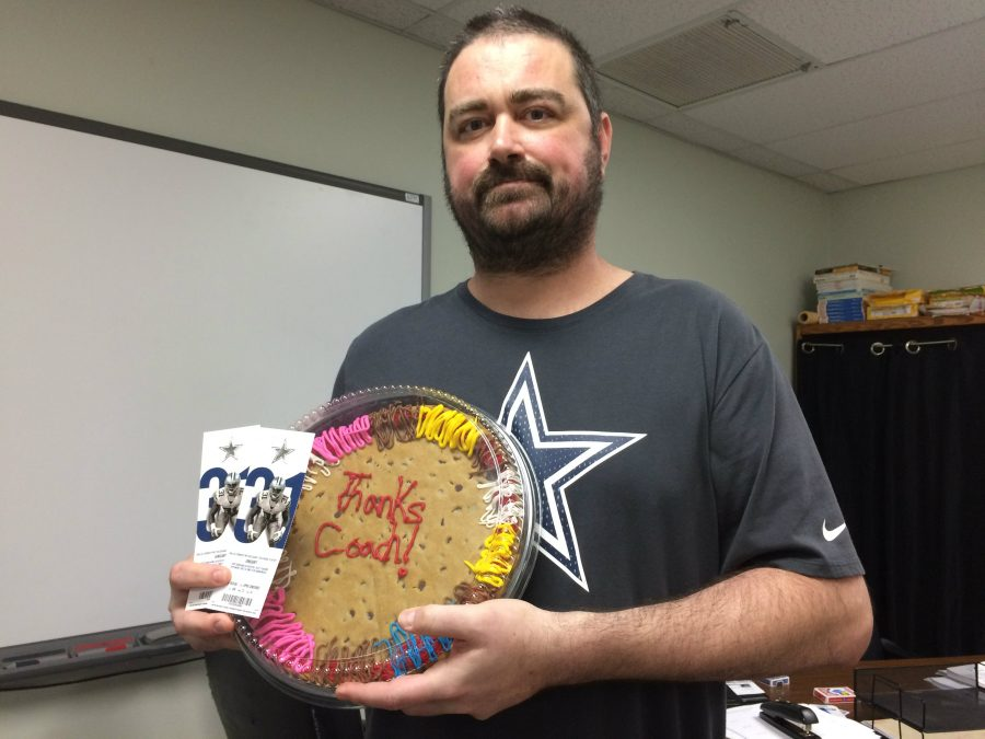 AP+Calculus+teacher+coach+Kirk+Richardson+shows+off+the+Dallas+Cowboys+football+tickets+and+cookie+cake+that+his+students+all+gifted+him+with+Thursday+morning+in+his+classroom.+As+a+lifelong+Cowboys+fan%2C+Richardson+was+surprised+when+he+walked+into+his+classroom+and+saw+the+gift+awaiting+him.+