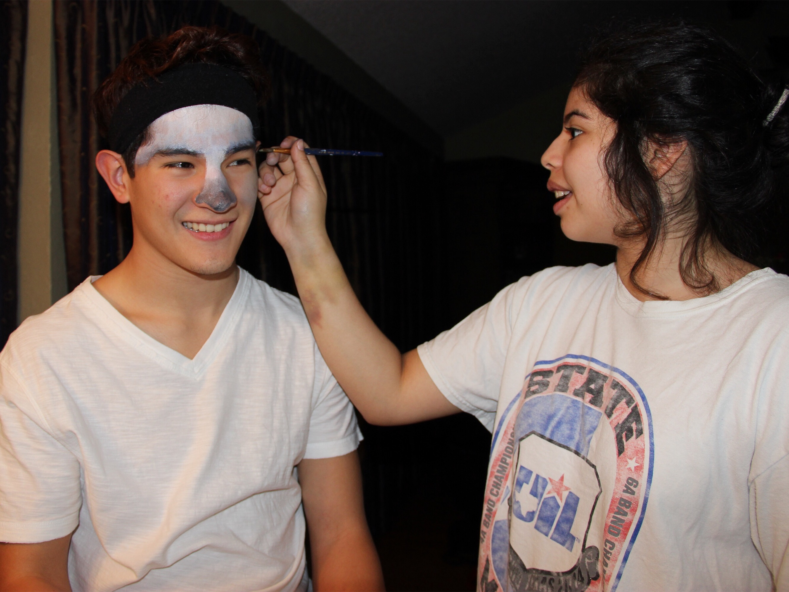 Coppell High School junior Jasmine Diaz paints on senior Brandon Medel's face on Tuesday night at her house. Diaz is part of the CHS art program, and is creating her Visual Arts Scholastic Event (VASE) project.