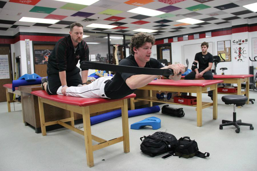 Coppell High School senior varsity baseball player Jacob Nesbit stretches out his back with the help of head athletic trainer Barry Jones. Nesbit is working his way to a full recovery and plans to further his career in baseball in college.