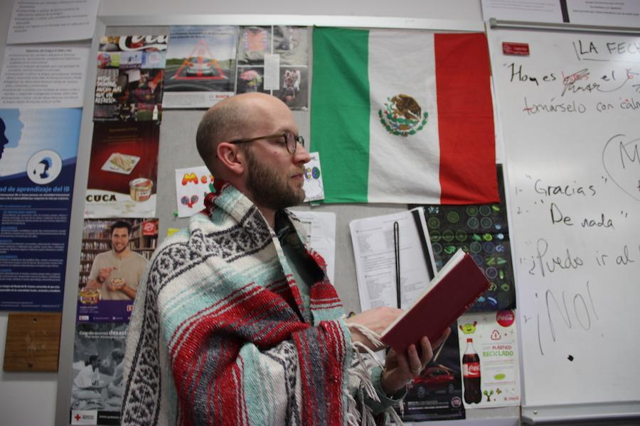 Coppell High School IB Spanish teacher Creighton Hulse shows off his blanket from Mexico in front of the Mexican flag hanging in his room. Hulse has taught in many different countries and uses his experiences to help teach students at Coppell.