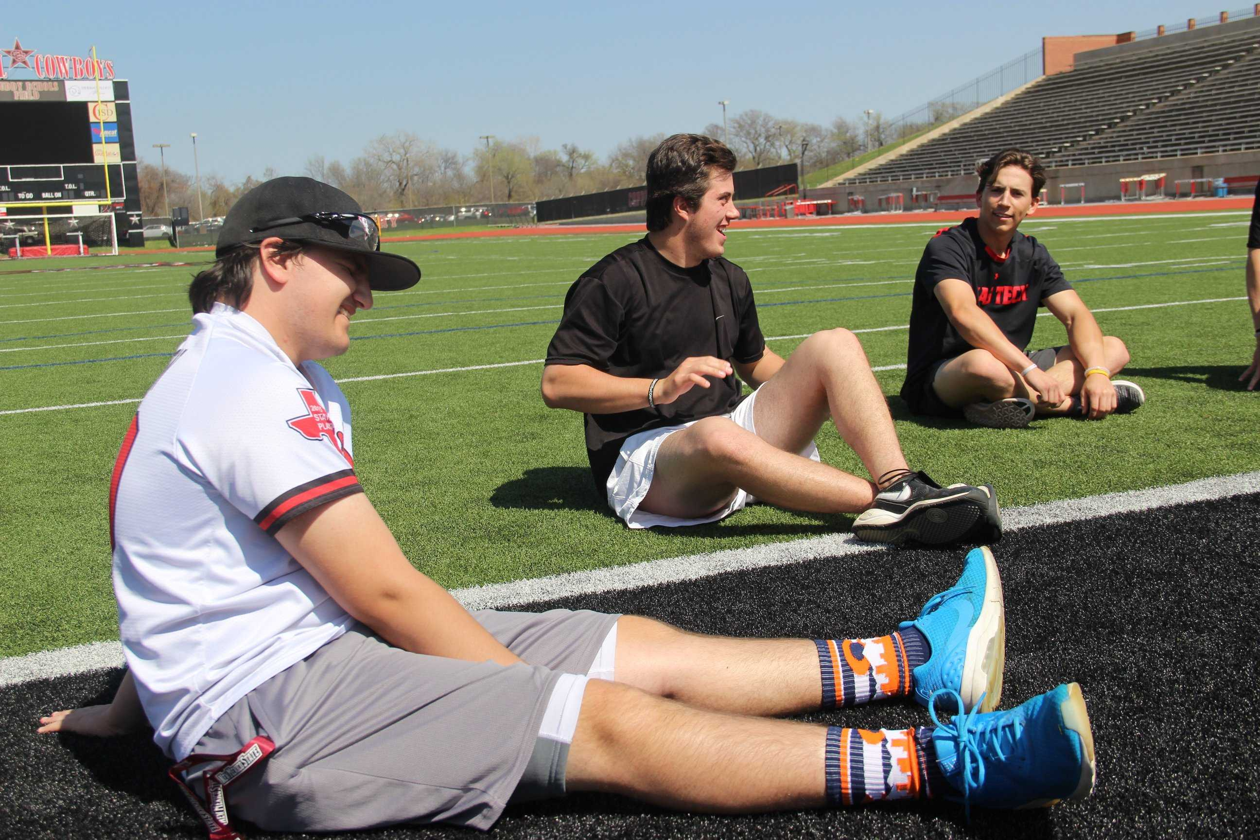 Coppell High School sophomore Christopher Jackson and seniors Davis Green and Mason Holt hang out outside on Buddy Echols Field during fourth period on Wednesday. Jackson is the team manager for the varsity baseball team.