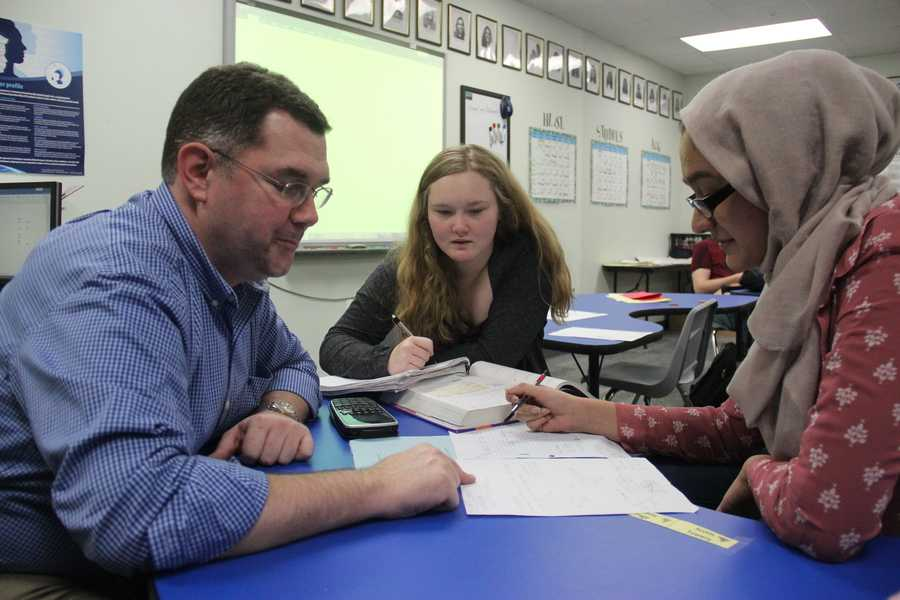 IB Math Studies teacher Ian VanderSchee works with seniors Jess Goode and Maria Khan on their trigonometry homework. VanderSchee teaches using the flipped classroom method, where students learn the material at home through videos and can ask questions and work out problems with him during class.