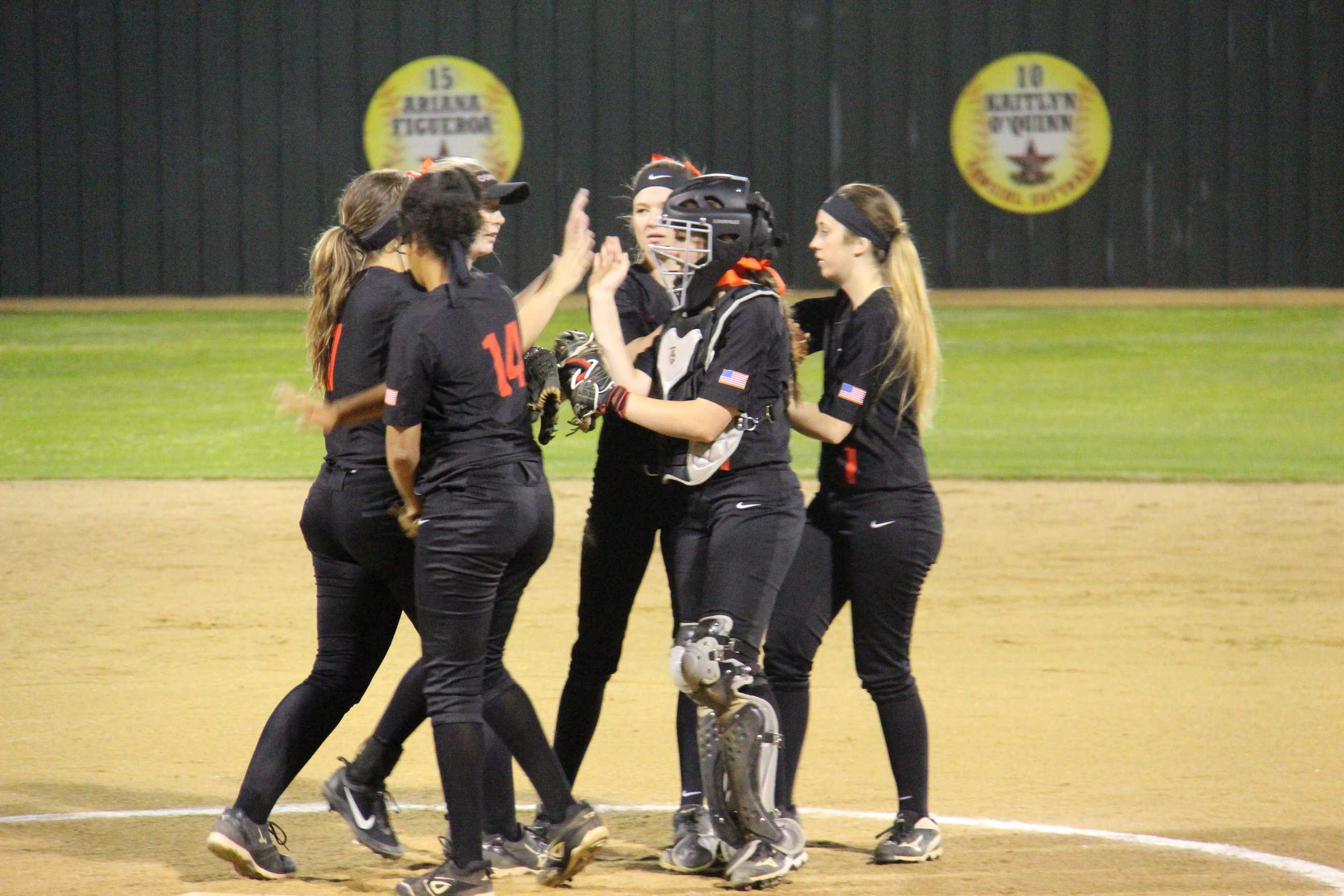 The Coppell Cowgirls come together on the field during the second inning of Friday night's District 9-6A opener against Richardson Pearce. The Cowgirls defeated the Lady Mustangs, 8-5.