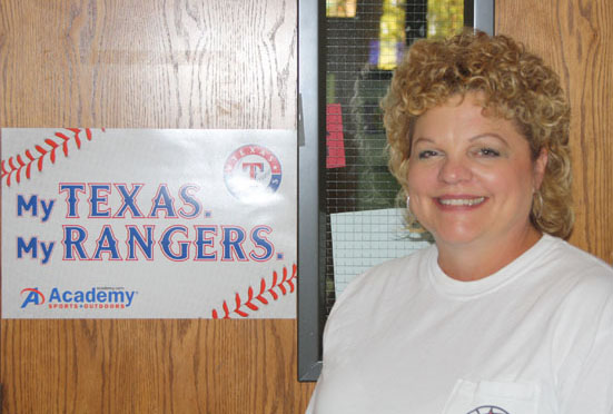 Mrs. Jackson poses in front of her classroom door next to her beloved Texas Rangers poster. Jackson recently won teacher of the month for October. Photo by Trevor Stiff.
