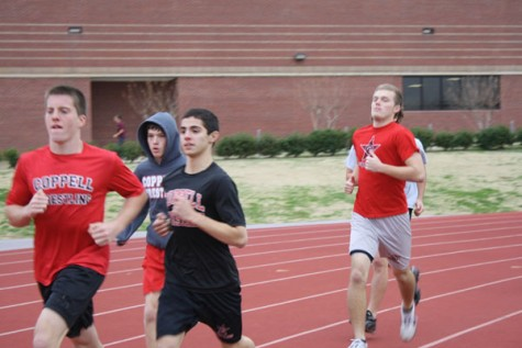 The Coppell varisty boys wrestling team warms up for a day of practice by running a few laps around the track. Photo by Ivy Hess.
