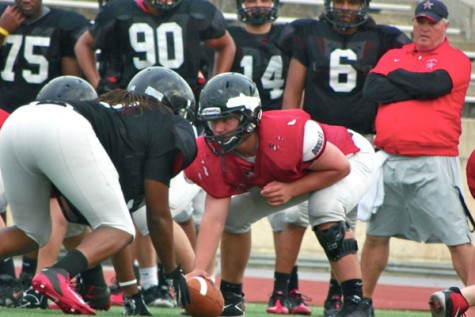 Junior center Leighton Light (in red) lines up and prepares for the next snap in spring football practice as Assistant Coach Steven Fex looks on. Photo by Trevor Stiff.
