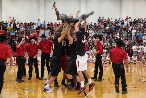 Coppell football players take down the Allen Eagle at Friday's pep rally