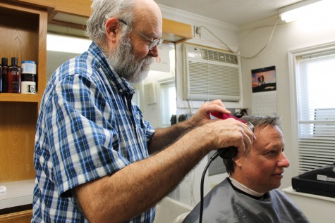 Photo by Mia Ford. Joe Shirley, owner of the Bethel Road Barber Shop, works his magic on his regular customer. Shirley runs a simple shop and strives to provide his customers with the best service possible.