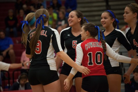 Teammates pat each other on the back after scoring a point against the Marcus volleyball team. Photo by Lauren Ussery.