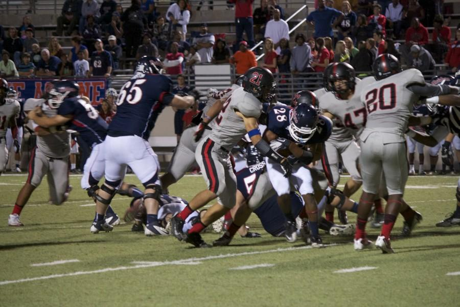 The Coppell Cowboys try to get the ball from the Denton Ryan Red Raiders. Cowboys won, 21-3, making the Cowboys the district champions. Photo by Regan Sullivan.