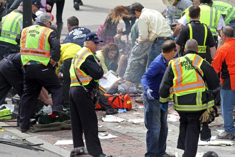 Emergency personnel assist the victims at the scene of a bomb blast during the Boston Marathon in Boston, Massachusetts, Monday, April 15, 2013. (Stuart Cahill/Boston Herald/MCT)