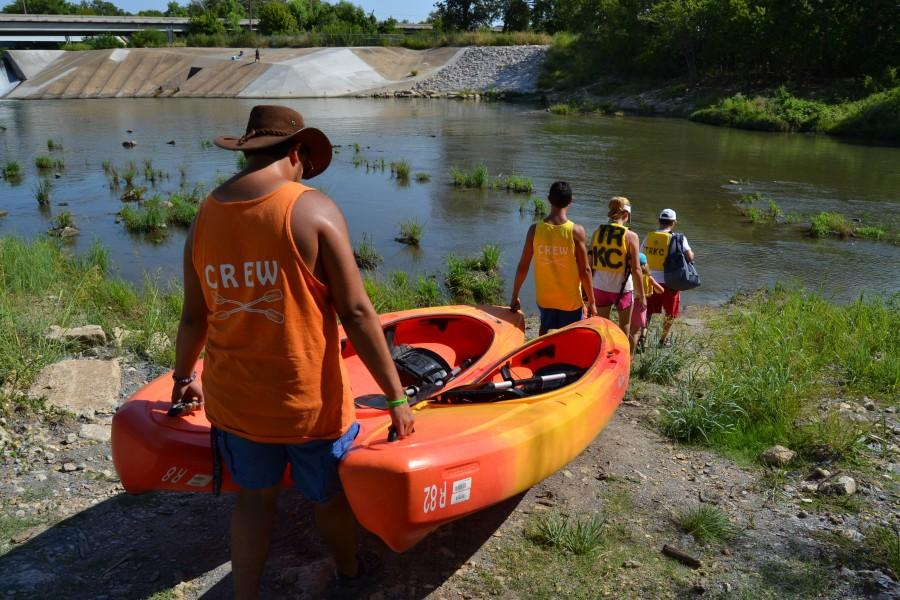 Trinity+River+Kayak+Co.+employees+A.J.+Date+and+Greg+Ludden+lead+a+family+down+to+the+river%2C+bringing+with+them+the+kayaks+the+customers+will+be+using.+The+family+spent+around+three+hours+kayaking+down+the+Trinity+River+on+Sunday+morning.+Photo+by+Sandy+Iyer.