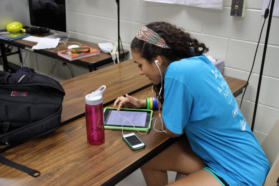 Junior Jordan Logan uses music to help her write her script in KCBY on Thursday.