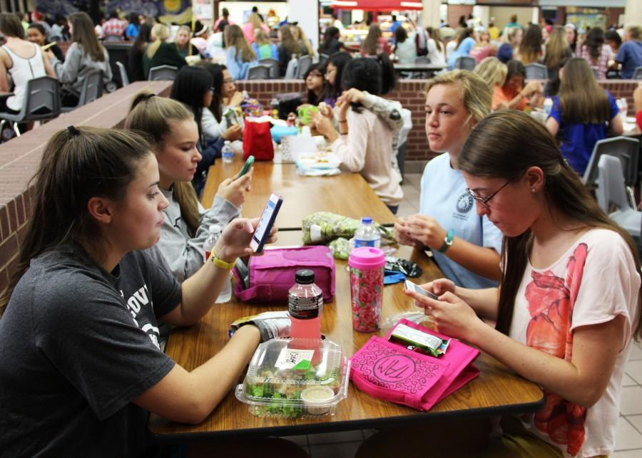 Juniors Caitlin Nutt, Ali Conte and Taylor Abramson take B lunch on Thursday to  catch up on social media while junior Kaylee Geiser attempts to catch up with her friends. Photo by Nicole Messer.