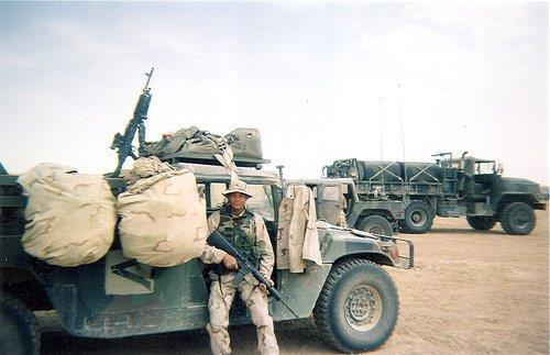 Student Resource Officer Ricky Jimenez poses in front of the fuel truck he drove while he served in Iraq. Photo courtesy Ricky Jimenez.