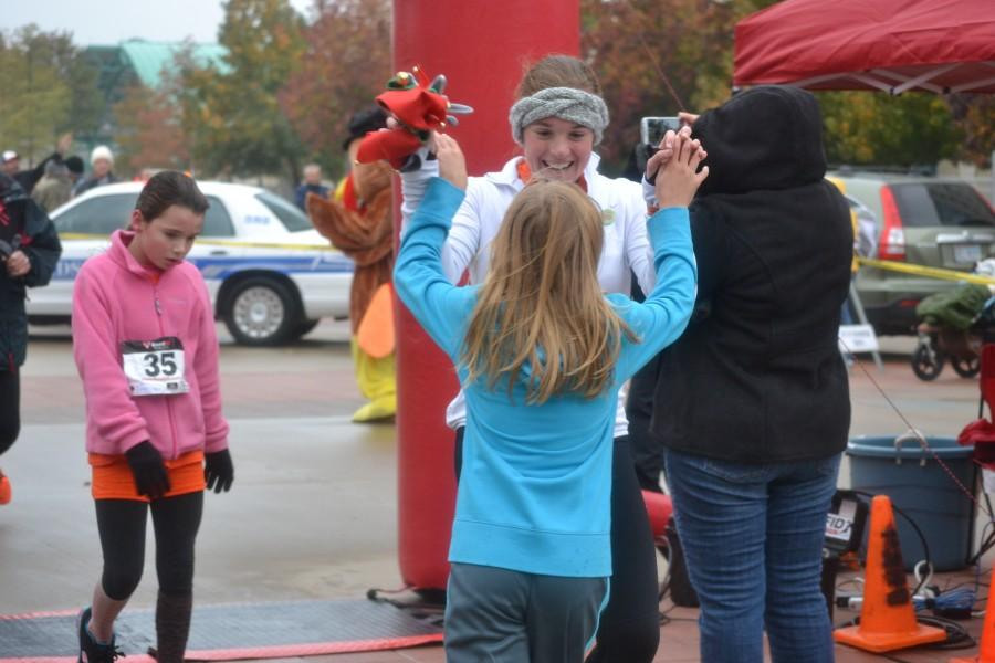 Junior Jessie Cranmer high fives fourth grader Abby Hendricks as they cross the finish line at the Gobble Hobble 5K on Nov. 23. Photo by Elizabeth Sims.