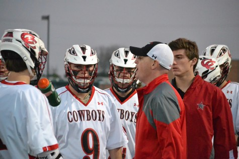 Head coach Alexander Poole discusses game strategy during a time out in the second quarter. The Cowboys fell to the Highland Park Scots, 8-5.