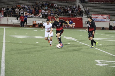 Junior forward Colton Clark dribbles past a Grapevine defender Victor Herrera on Thursday at Mustang-Panther Stadium. The Cowboys, a 3-1 winner over the Mustangs, face Mansfield at 8 p.m. Thursday at Irving Schools Stadium in the class 5A area playoffs. Photo by Shannon Wilkinson.