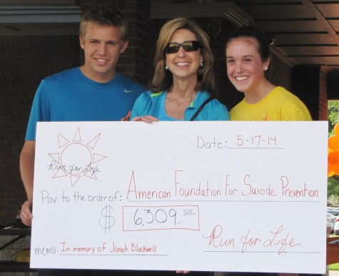 Junior Jessie Cranmer and Senior George Fairchild present a check of $6,309 to the American Foundation for Suicide Prevention on Saturday, May 17 after hosting the Run for Life 5K in honor of Jonah Blackwell. Photo by Kara Hallam