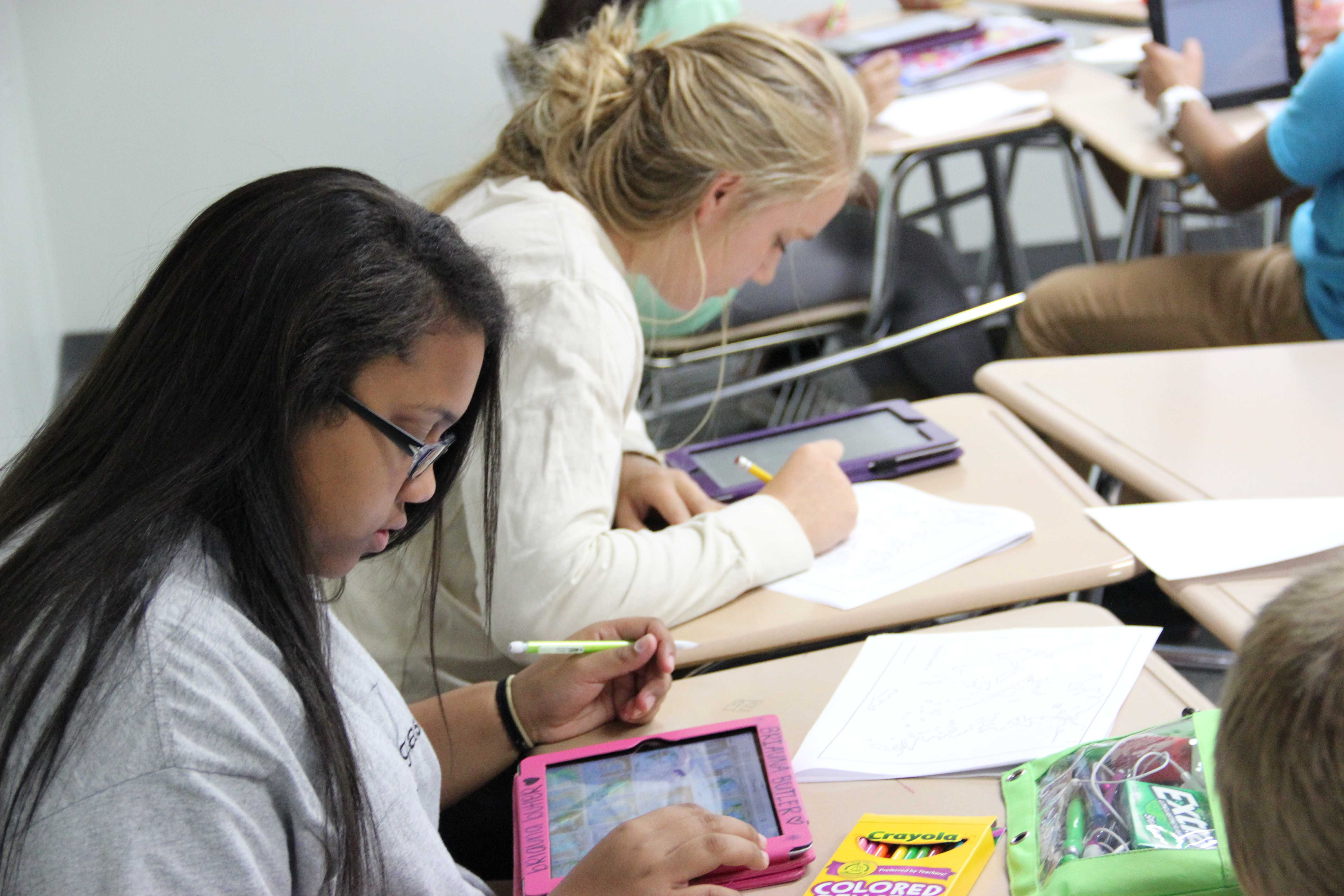 Sophomores Briauna Butler and Lara Collins work together in Mrs. Leyendecker's U.S. history class by using their iPads to help them label an assignment. Photo by Chelsea Banks