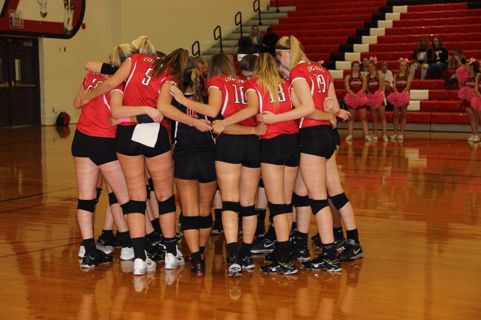 Coppell High School Cowgirl varsity volleyball team huddles to talk and congratulate each other after the win against Trinity High School. The Cowgirls won all three sets, the first with a score of 25-9, 25-17, and 25-11 on Friday night's game in the CHS large gym. Photo by Megan Winkle.