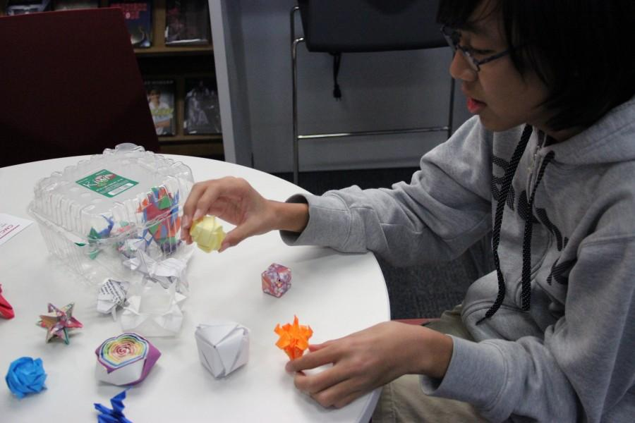 """Coppell High School sophomore Frank Zhang displays his origami pieces on a table at the library on Nov.18. """"The feeling of satisfaction when I complete a really difficult model is the best feeling ever,"""" Zhang said """"Everybody has something they enjoy as a hobby and for me, that's origami."""" Photo by Ayoung Jo."""