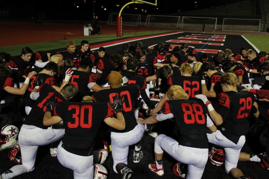 Coppell+High+School+varsity+football+players+come+together+before+the+game+against+Haltom+to+pray.+After+the+last+home+game+at+Buddy+Echols+Field+for+this+season+The+Cowboys+beat+The+Buffalos+44-5+on+Friday+night.+Photo+by+Megan+Winkle%0A