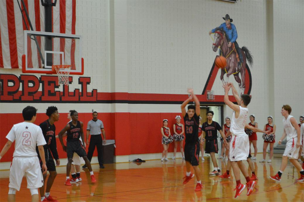 Coppell High School senior shooting guard Alex Vuchkov sinks a basket during the fourth quarter of Friday night's home game played in the Coppell High School Large gym against the Trinity Trojans. The Cowboys beat the Trojans in a close 49-45 game.