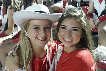 Helena Posey (left) and Charlotte Posey (right)  hug at a game. Helena, a Lariette, was there to support the team.