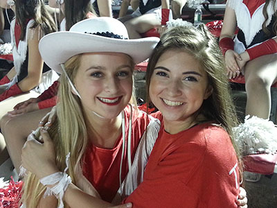 Senior Helena Posey (left) and freshman Charlotte Posey (right) hug at a game. Helena, a Lariette, was there to support the team, and Charlotte was there to support Helena.