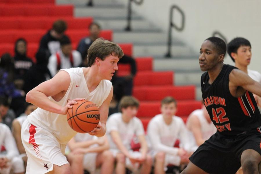 Coppell High School junior and forward Sam Marshall attempts to dribble around Haltom High School senior Emmanuel Egneti during the first quarter of Friday night's game in the CHS large gym. Coppell took the win over Haltom with a final score of 50-45, moving to 6-0 in district play.
