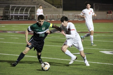 Coppell High School senior and fullback Brandon Bohn attempts to steal the ball from a Carroll High School forward during the first half of Friday night's game at Buddy Echols Field. The Coppell Cowboys claimed a victory over the Southlake Carroll Dragons with a final score of 6­-0.