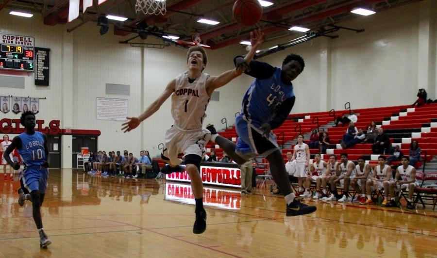 Coppell+High+School+sophomore+Parker+Rodman+attempts+to+get+the+rebound+as+he+is+being+guarded+in+the+CHS+large+gym+during+Tuesday+night%E2%80%99s+game.+The+Coppell+Cowboys+ended+the+game+with+a+score+of+50-49%2C+claiming+a+victory+over+the+Blue+Raiders.