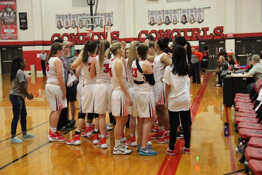 Coppell High School varsity basketball Cowgirls come together for a timeout during the second quarter. The Cowgirls lost to the Lady Buffalo with a final score of 43-35. Photo by Megan Winkle