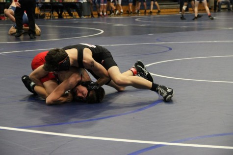 Coppell High School freshman Brady Schneider wrestles against Hebron Hawks JV wrestler in the navy gym at Flower Mound High School. The JV wrestling team competed in the District 6 JV Championships Wednesday.