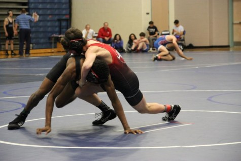 Coppell High School sophomore Hudson Brock (red) wrestles against Coppell wrestler freshman Josh Williams (black) in the navy gym at Flower Mound High School. The JV wrestling team competed in the District 6 JV Championships Wednesday.