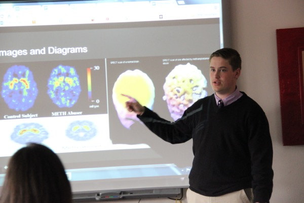 Anatomy & physiology senior student Nathan Ballard demonstrates a diagram of what your brain looks like before and after the use of methamphetamine on Tuesday. Stefanie Clarke's class is currently learning about how different drugs affect your nervous system.