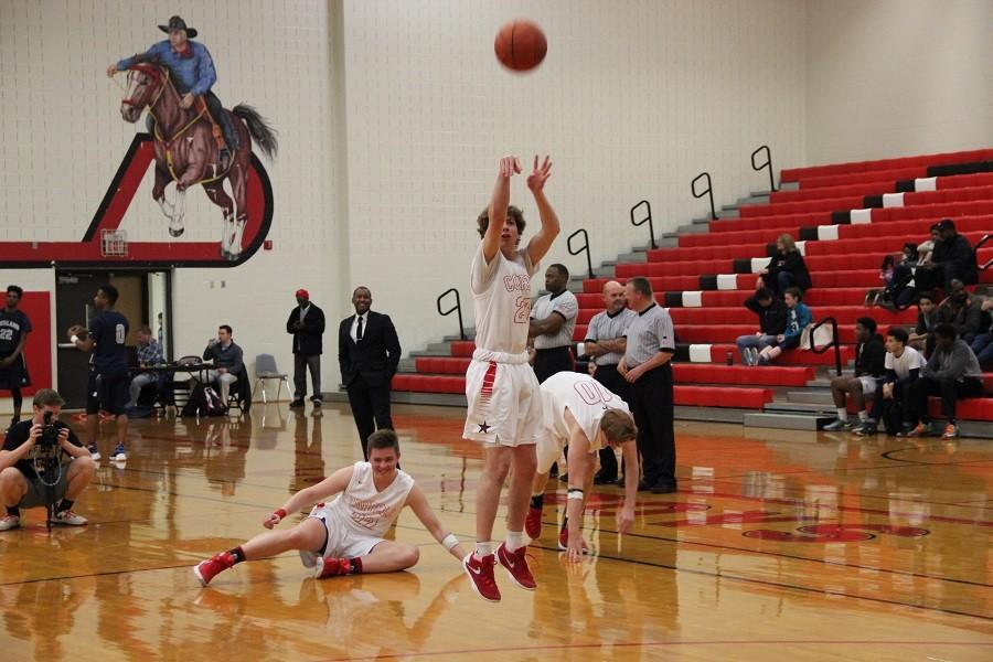 Coppell High School junior Caden Horak warms up before a game by shooting three pointers on Friday. Coppell defeated Richland 53-50 in the big gym at Coppell High School.