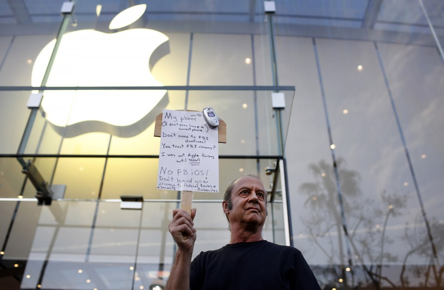 Tom Wolff holds a sign in support of Apple outside of the the Apple store in Santa Monica, Calif., on Tuesday, Feb. 23, 2016. Rallies were planned at Apple stores across the country to support the company's refusal to help the FBI access the cell phone of a gunman who took part in the killings of 14 people at the Inland Regional Center in San Bernardino. (Katie Falkenberg/Los Angeles Times/TNS)