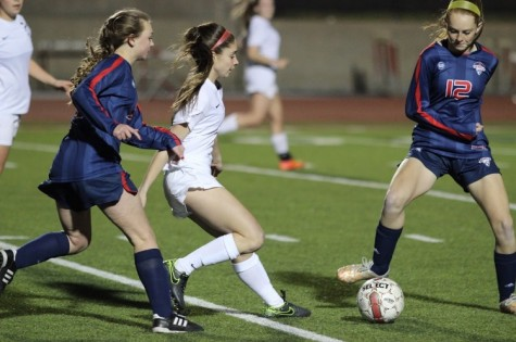Coppell High School freshman Nicole Henry dodges two oncoming Richland defenders during the second half of Friday night's game. The Coppell Cowgirls defeated the Richland Rebels with a final score of 8-0 at Buddy Echols Field.