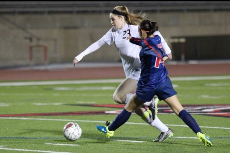 Coppell High School junior Sarah Houchin runs the ball down the field while a Richland defender chases after her as the first half of Friday night's game comes to a close. Coppell constantly held the lead over Richland, finishing the game with a score of 8-0 at Buddy Echols Field.