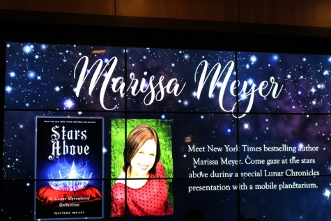 A digital poster inside the South Irving Library displays information about Marissa Meyer before her talk about her new book, Stars Above. The new novel is a collection of short stories set in the same world as The Lunar Chronicles. Meyer came to Irving on Saturday for her fifth stop on her Stars Above Tour. Photo by Kelly Monaghan.