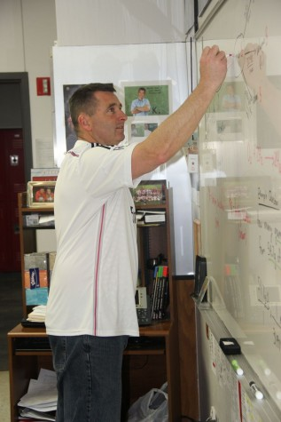 Coppell High School chemistry teacher Chris Stricker helps students better their education during class on Friday. Stricker was a former soccer coach and retired that position last year after winning the Cowgirls won state.