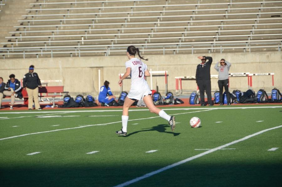 Coppell+High+School+senior+Kate+Kaiser+runs+to+kick+the+soccer+ball+on+March+24+at+Buddy+Echols+field.+Coppell+Cowgirls+defeated+Duncanville+1-0+in+the+first+round+of+playoffs.